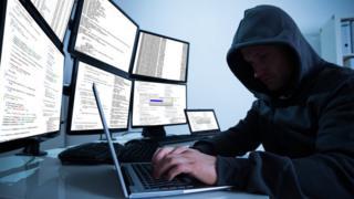 Hooded hacker on laptop i nfront of bank of desktop monitors