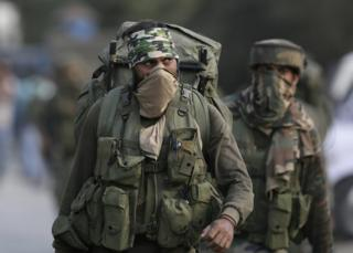Indian soldiers leave the site of a gun battle in Pampore, on the outskirts of Srinagar, Indian-controlled Kashmir, 12 October