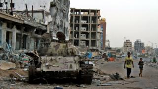 Young Yemenis walk past a tank destroyed in clashes between Houthi rebels and government forces in the port city of Aden - 19 August 2015