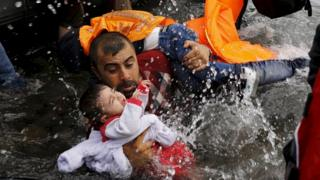 A Syrian refugee holds on to his children as he struggles to walk off a dinghy on the Greek island of Lesbos, 24 Aug