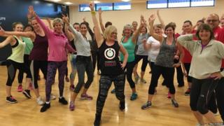 Fitness instructor Tina Donkin posing with her Zumba class
