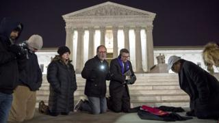 People pray in front of the US Supreme Court after the death of Justice Antonin Scalia