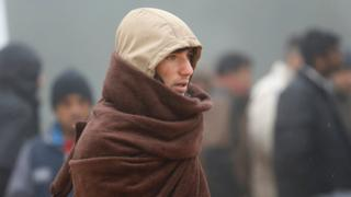 A migrant wraps-up against the cold weather, at a temporary registration centre in the village of Schwarzenborn, northeast of Frankfurt, Germany October 15, 2015.