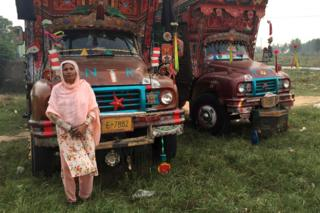 Shamim standing in front of trucks