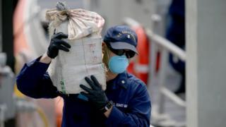 A US Coast Guard officer carries a bundle of seized cocaine
