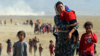 Displaced Yazidis fleeing Islamic State militants in Sinjar, Iraq, walk towards the Syrian border (11 August 2014)