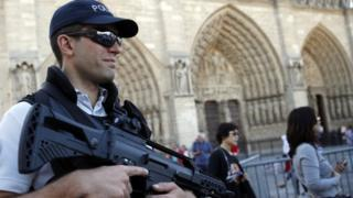 A French police officer patrols in front of Notre Dame cathedral, in Paris, Friday Sept. 9, 2016.