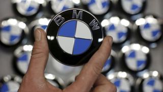 Hand holding round BMW logo