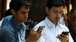Indian pedestrians check their cellphones