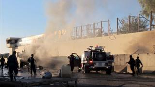 Afghan security forces try to douse a fire after a suicide car bomb blast attacked a military convoy in Lashkar Gah