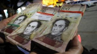 A woman shows wads of 100-bolivar-bills to change in La Parada, municipality of Villa del Rosario, Norte de Santander department, Colombia, in the border with Venezuela, on December 11, 2016.