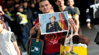 Refugee arriving in Germany holds up crumpled picture of Angela Merkel