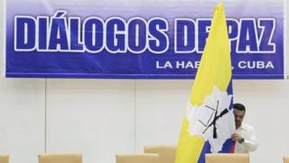 A man puts up a Farc flag up before a news conference in Havana on 23 September, 2015.