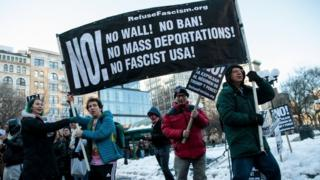 Demonstrators in New York hold up a banner during a protest against President Donald Trump's proposed travel ban, 17 March 2017
