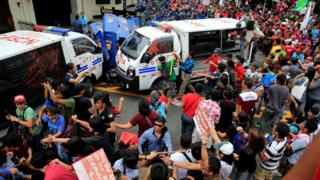 """Protesters try to trash a police mobile patrol vehicle as they join various activist and Indigenous People""""s (IP) groups in a protest against the continuing presence of U.S. troops in the Philippines in front of the U.S. Embassy in metro Manila, Philippines October 19, 2016"""