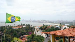 A Brazilian flag flying over a house with the coastal line of Recife seen in background in the north-eastern Brazilian city of Olinda in the state of Pernambuco, September 2010.