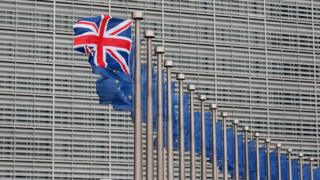 The union flag flying next to a row of EU flags