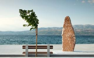 A sculpture and a tree in front of the sea in Supetar, Croatia