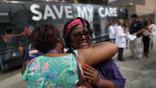 Margalie Williams, a cancer survivor, is hugged after speaking during a rally near Jackson Memorial hospital in Miami, Florida.