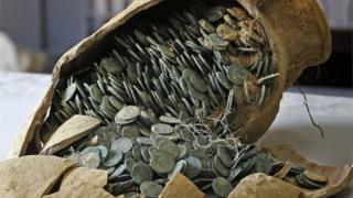 Roman bronze coins held in a cracked jar