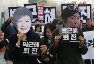 In this 18 November 2016, file photo, protesters wearing masks of South Korean President Park Geun-hye, left and Choi Soon-sil, Park's long-time friend, in Seoul, South Korea.