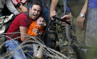 A migrant man and boy blocked by Macedonian police near Idomeni, northern Greece, 21 August 2015