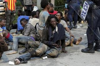 Migrants sit on the ground next to Spanish police officers after storming a fence to enter the Spanish enclave of Ceuta on 17 February 2017