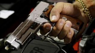 A customer looks at a SIG Sauer hand gun at a gun show held by Florida Gun Shows, Saturday, Jan. 9, 2016, in Miami