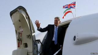 Britain's Foreign Secretary Philip Hammond waves as he boards a Royal Air Force aeroplane at Mehrabad Airport to leave Tehran