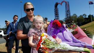 Local resident Nicole Baker and her daughter Charlize lay flowers at Dreamworld in Queensland, Australia on October 26, 2016 after four tourists were killed there.