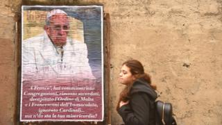 Woman walking past a poster of Pope Francis