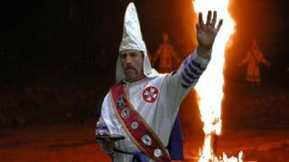 Frank Ancona, wearing a white hood and standing in front of a burning cross