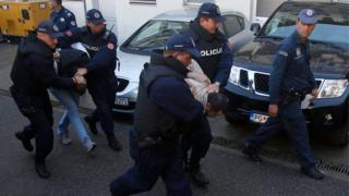 Montenegrin police officers escort men for questioning in Podgorica