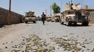 Bullet casings lie on the ground as Iraqi government forces near the Qayara airbase (14 July 2016)