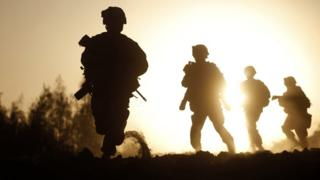 A silhouette of US soldiers in action in Afghanistan