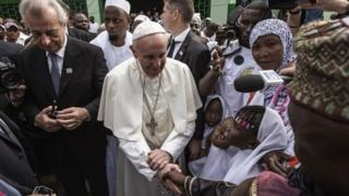 Pope Francis (C) shakes the hands of children upon his arrival to the Central Mosque in the PK5 neighborhood on November 30, 2015 in Bangui
