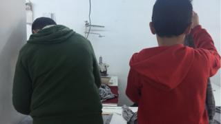 Syrian children Abdurrahman, 15, and Mohammed, 13, at work in an Istanbul garment factory