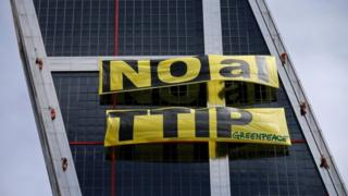 Greenpeace activists display a banner against TTIP free trade agreement while suspended on one of the Kio towers in Madrid, Spain