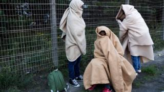 "Migrants, who say they are minors, use blankets to protect themselves from the cold on a street after the dismantlement of the ""Jungle"" camp in Calais, France, October 27, 2016"