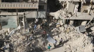 Men search for survivors in area hit in reported government air strike in rebel-held Tariq al-Bab district of Aleppo (26 September 2016)