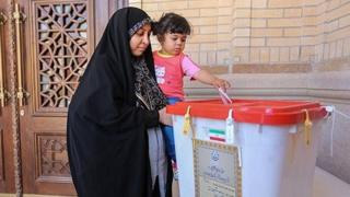 An Iranian woman holds a girl as she casts her vote during a second round of parliamentary elections, in Shiraz (30 April 2016)