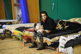 A woman holding a child in her arms sits on a bed as residents from the village of Montereale set up for the night in a large tent on a nearby sports ground in Montereale, Abruzzo, 18 January