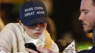 """A woman wears a cap with a China message that is reminiscent of the campaign slogan of US President-elect Donald Trump """"Make America Great Again,"""" at a bar in Beijing, China, 09 November 2016."""