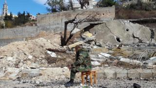 A pro-government soldier sits in a town damaged during Syria's war