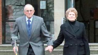 Kenneth Hugill, leaves court with his wife
