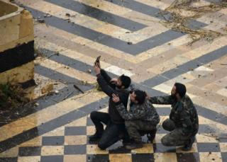 Syrian pro-government forces take a selfie in the courtyard of the ancient Umayyad mosque in the old city of Aleppo
