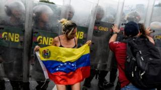 Members of the opposition of Venezuelan President Nicolas Maduro clash with riot police during a demonstration in Caracas on May 11, 2016.
