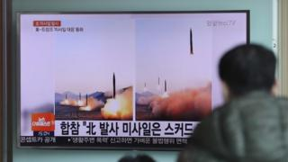 Man watches TV report on North Korean launches in Seoul