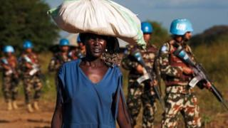 A displaced woman carries goods as UN peacekeepers patrol in Juba. Photo: 4 October 2016
