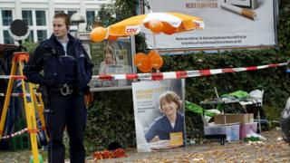 A police officer stands guard next to an election campaign poster of Henriette Reker in Cologne, Germany October 17, 2015.